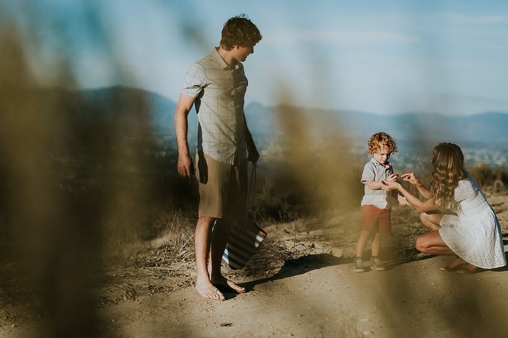 photo by Orange County family photographer Krystil McDowall. Candid photo of mom offering raspberries to her sweet boy while photographer takes a candid image peaking through the grass during outdoor family lifestyle photo session at Top of the World Laguna Beach California