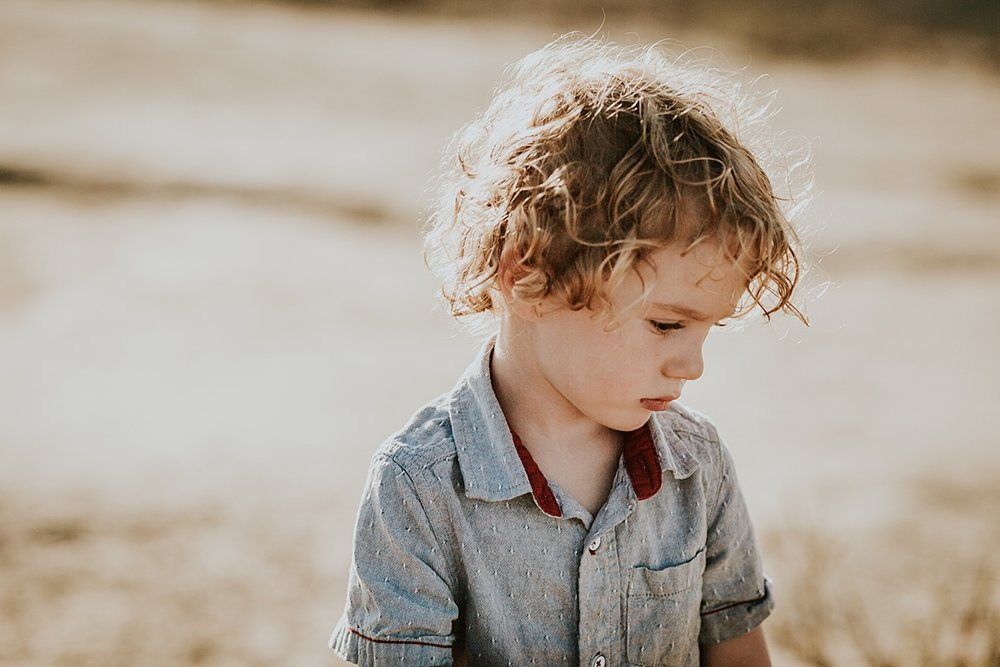 photo by Orange County family photographer Krystil McDowall. Portrait of son looking pensive standing in his blue button up shirt with the son streaming in the background at Top of the World Laguna Beach California
