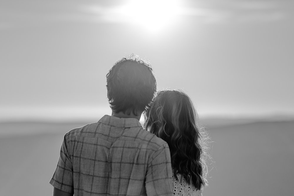 photo by Orange County family photographer Krystil McDowall. black and white photo of mom and dad looking at the mountains as the sun sets during family lifestyle photo session at Top of the World Laguna Beach California