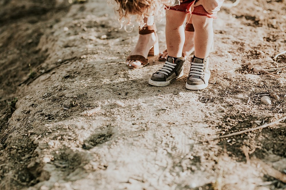 photo by Orange County family photographer Krystil McDowall. photo of mom and dad's feet standing on the dirt road at Top of the World Laguna Beach California