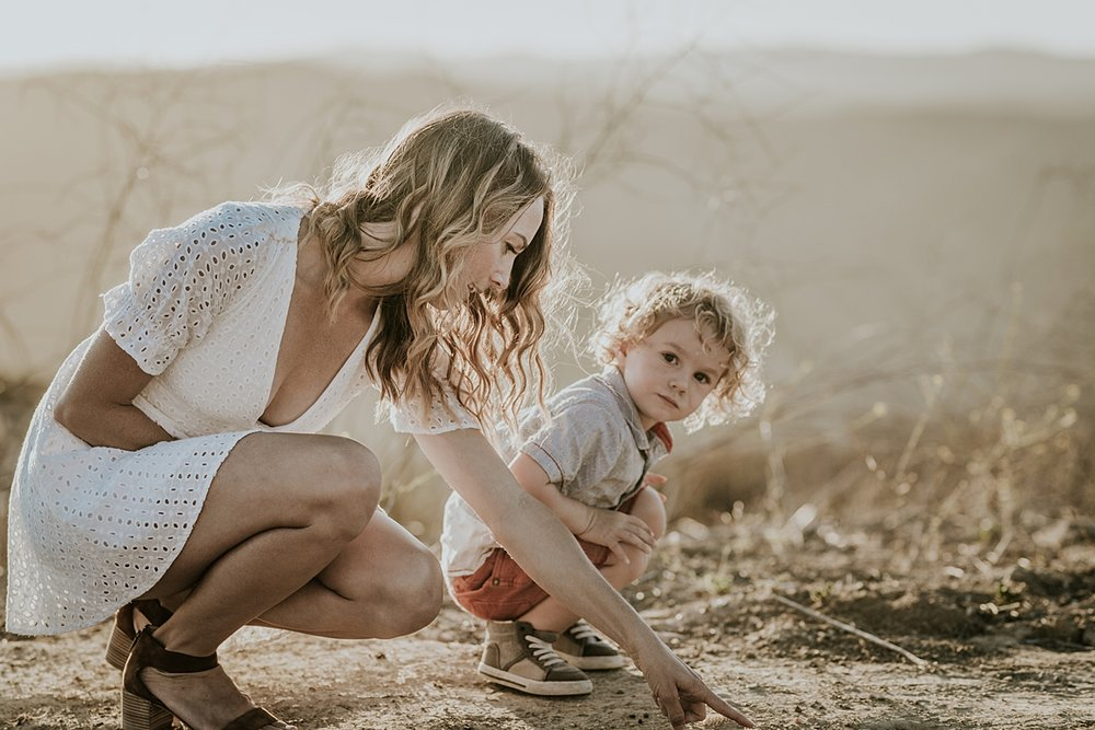 photo by Orange County family photographer Krystil McDowall. Candid photo of boy and his mom playing in the dirt at the mountain top during family lifestyle photo session at Top of the World Laguna Beach California