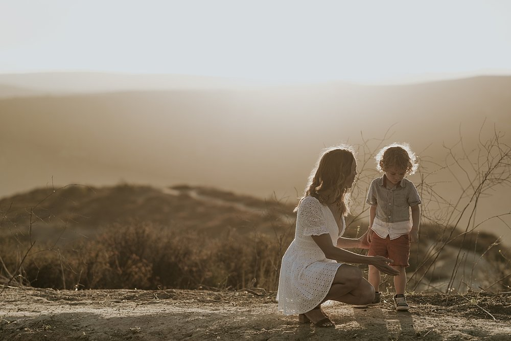 photo by Orange County family photographer Krystil McDowall Photography. Photo of mom and her son standing at the top of the hills as the sun sets during lifestyle family photo session at Top of the World Laguna Beach California