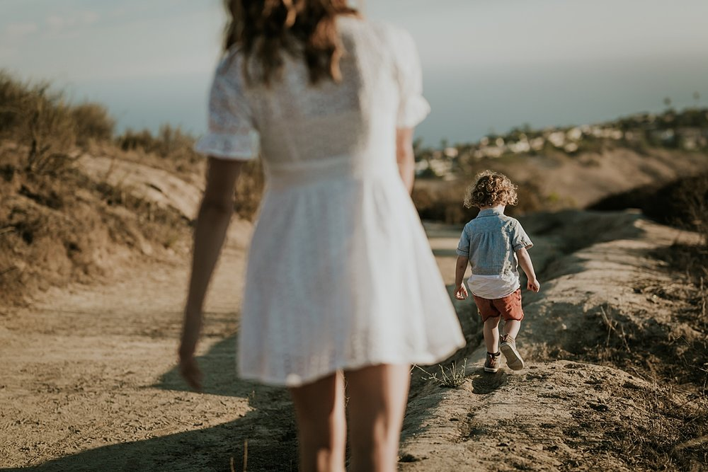 photo by Orange County family photographer Krystil McDowall Photography. Photo of mom chasing her son as he runs across the hilltops while the sun sets during lifestyle family photo session at Top of the World Laguna Beach California
