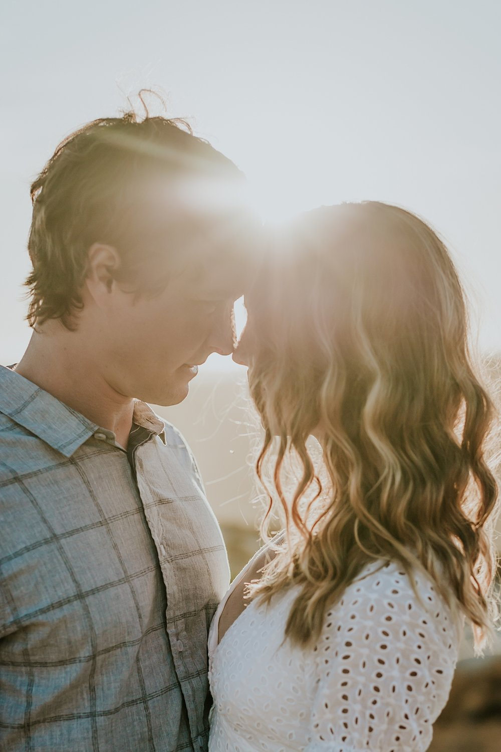 photo by Orange County family photographer Krystil McDowall Photography. Portrait of husband and wife standing as their foreheads touch and the sun peaks through the background during lifestyle family photo session at Top of the World Laguna Beach California