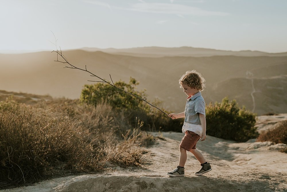 photo by Orange County family photographer Krystil McDowall Photography. Portrait of young boy holding stick as he runs around the mountains at Top of the World Laguna Beach California