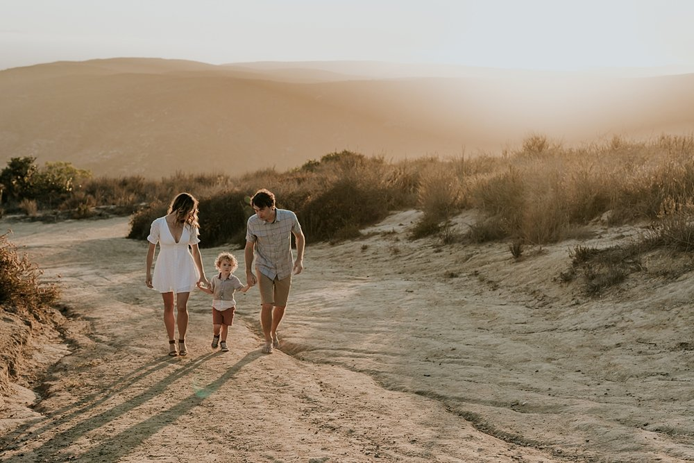 photo by Orange County family photographer Krystil McDowall Photography. photo of family of three holding hands and walking up the dirt road at Top of the World Laguna Beach California