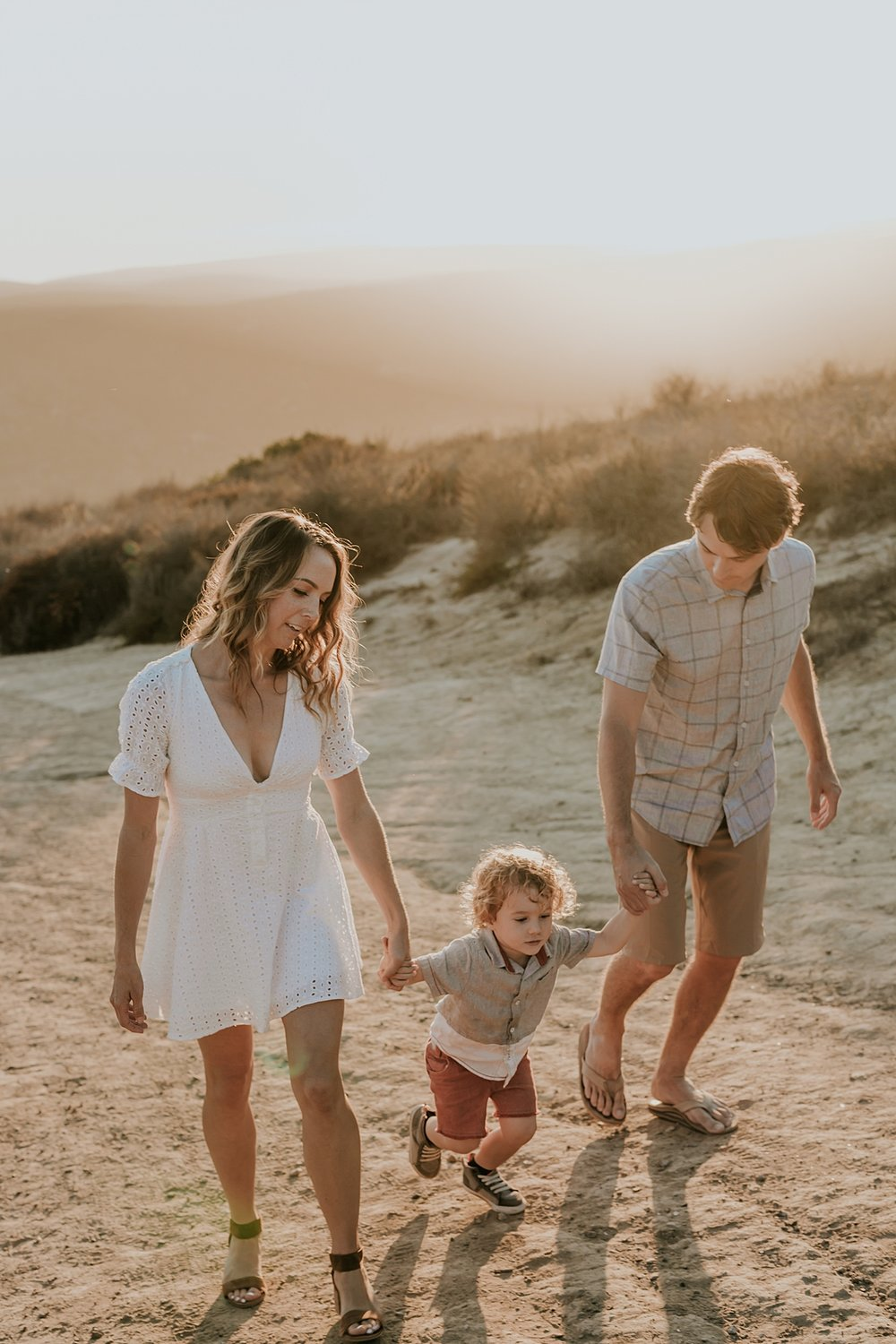 photo by Orange County family photographer Krystil McDowall Photography. close up photo of family of three holding hands and walking up the dirt road at Top of the World Laguna Beach California