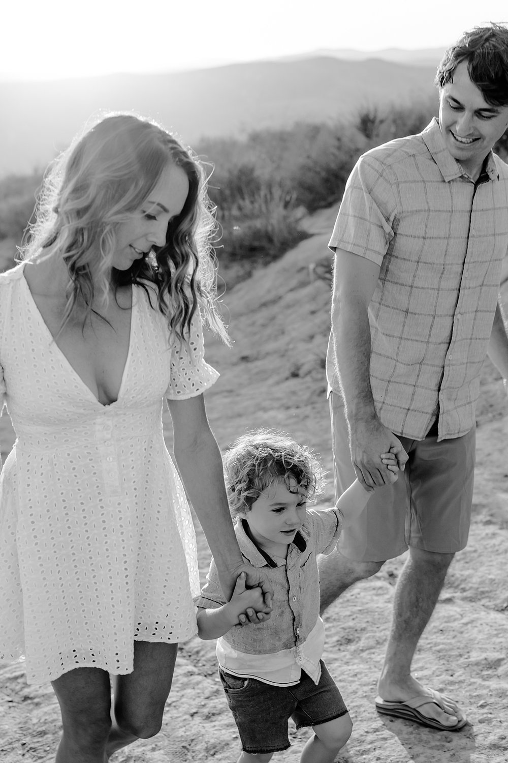 photo by Orange County family photographer Krystil McDowall Photography. black and white photo of family of three holding hands and walking up the dirt road at Top of the World Laguna Beach California