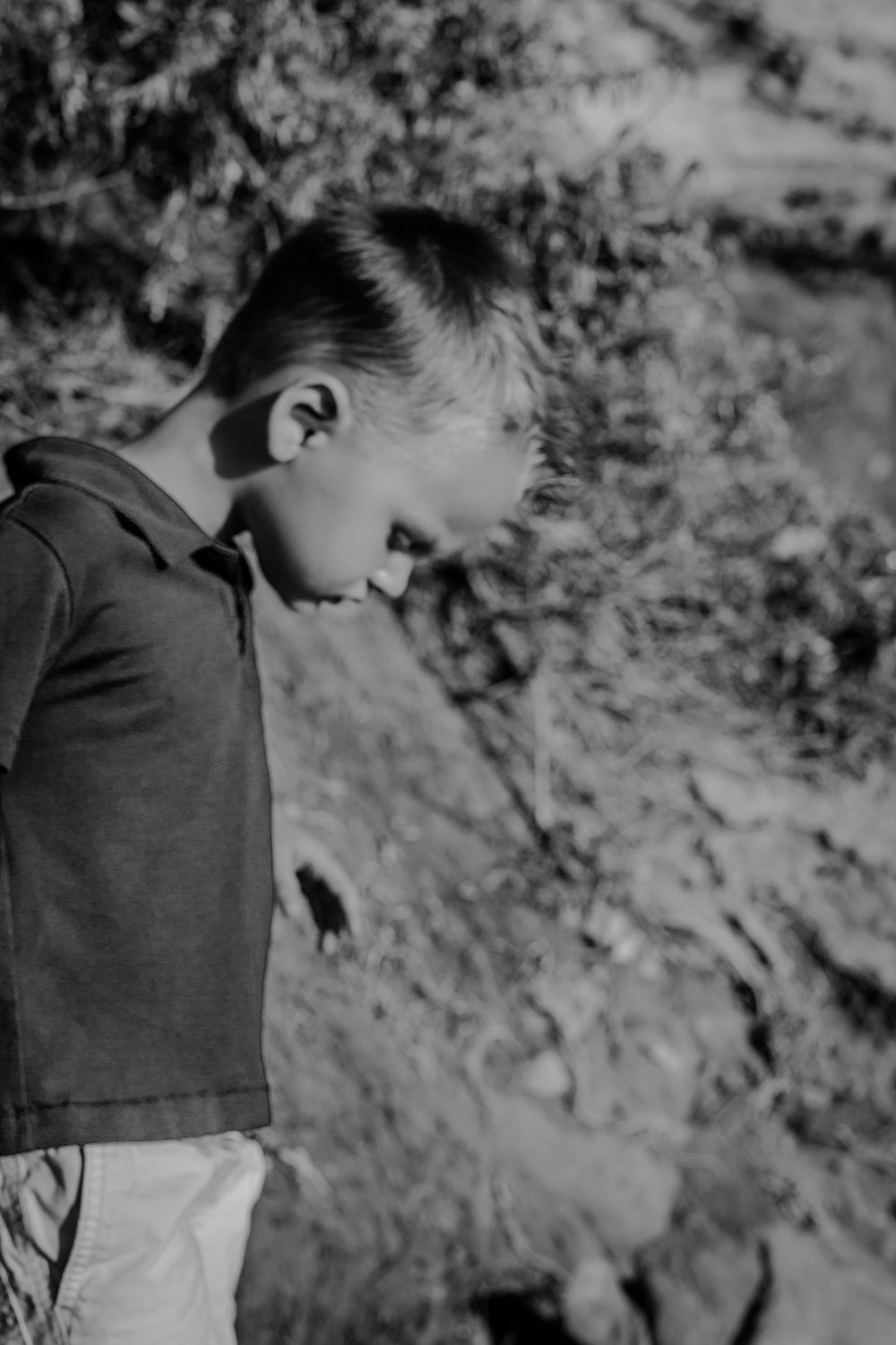 orange county family photographer. blurred black and white photo of boy standing at the beach during outdoor family photo session at Corona del Mar State Beach with Krystil McDowall Photography