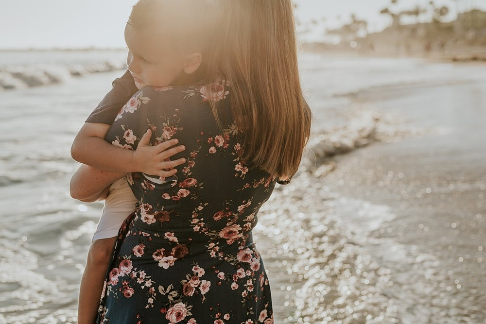 orange county family photographer. photo of mom holding her super cute son in the ocean surf as the sun begins to set during outdoor family photo session at Corona del Mar State Beach with Krystil McDowall Photography