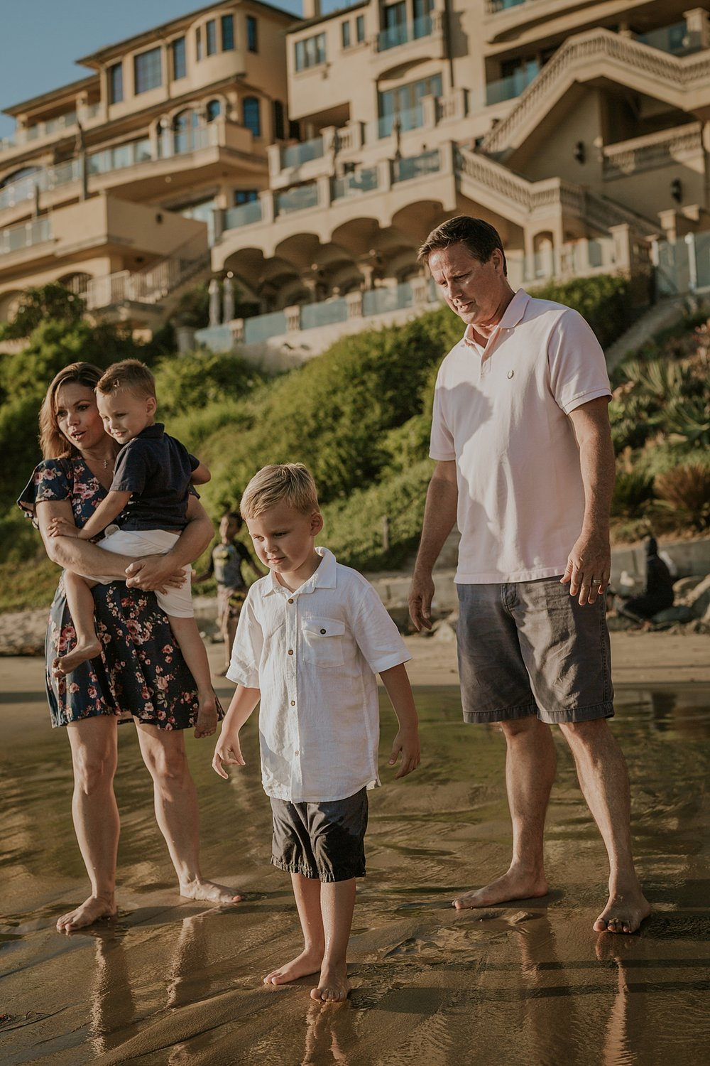 orange county family photographer. family photo of mom, dad and their boys playing in the sand during outdoor family photo session at Corona del Mar State Beach with Krystil McDowall Photography
