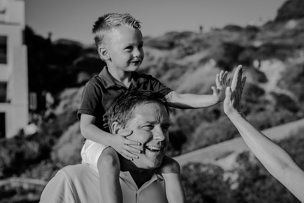 orange county family photographer. photo of dad giving his son a shoulder ride while he high 5's his mom during outdoor family photo session at Corona del Mar State Beach with Krystil McDowall Photography