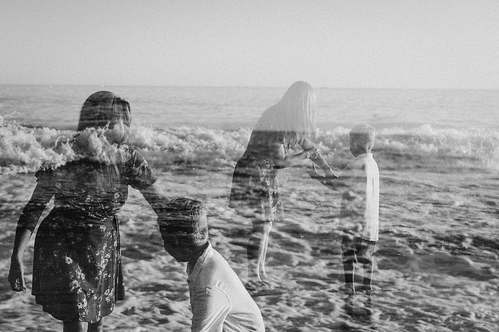 orange county family photographer. double exposure photo of mom and her son playing in the shallow ocean waves at Corona del Mar State Beach