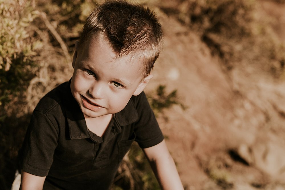 orange county family photographer. portrait of young boy with beach bluffs in the background at Corona del Mar State Beach with Krystil McDowall Photography
