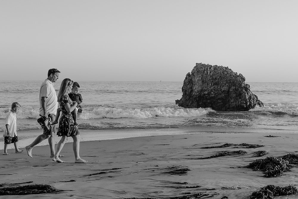 orange county family photographer. candid black and white photo of family as they walk along the beach during outdoor family photo session at Corona del Mar State Beach with Krystil McDowall Photography