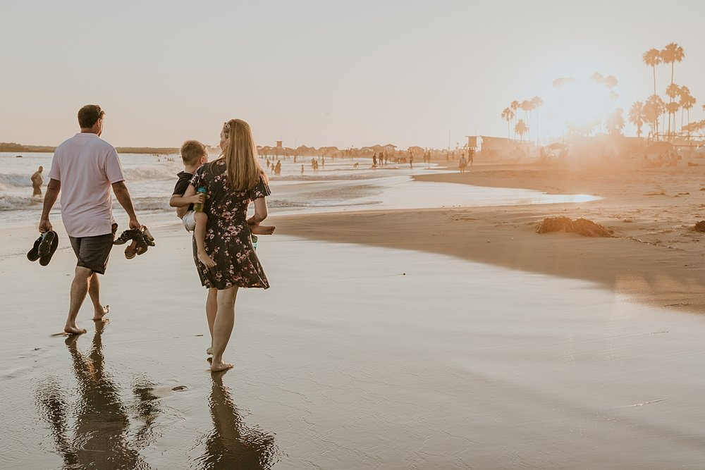 orange county family photographer. candid photo of mom and dad as they walk along Corona del Mar State Beach with Krystil McDowall Photography