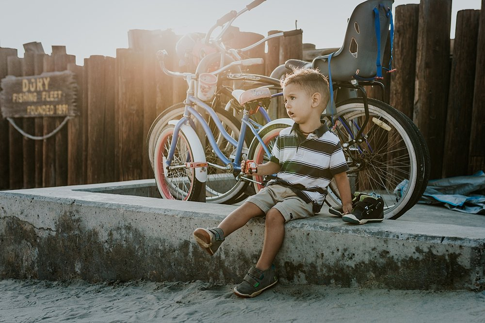 Orange County family photographer. Photo of sweet toddler sitting near bike rack at Huntington Beach Pier during outdoor family photo session