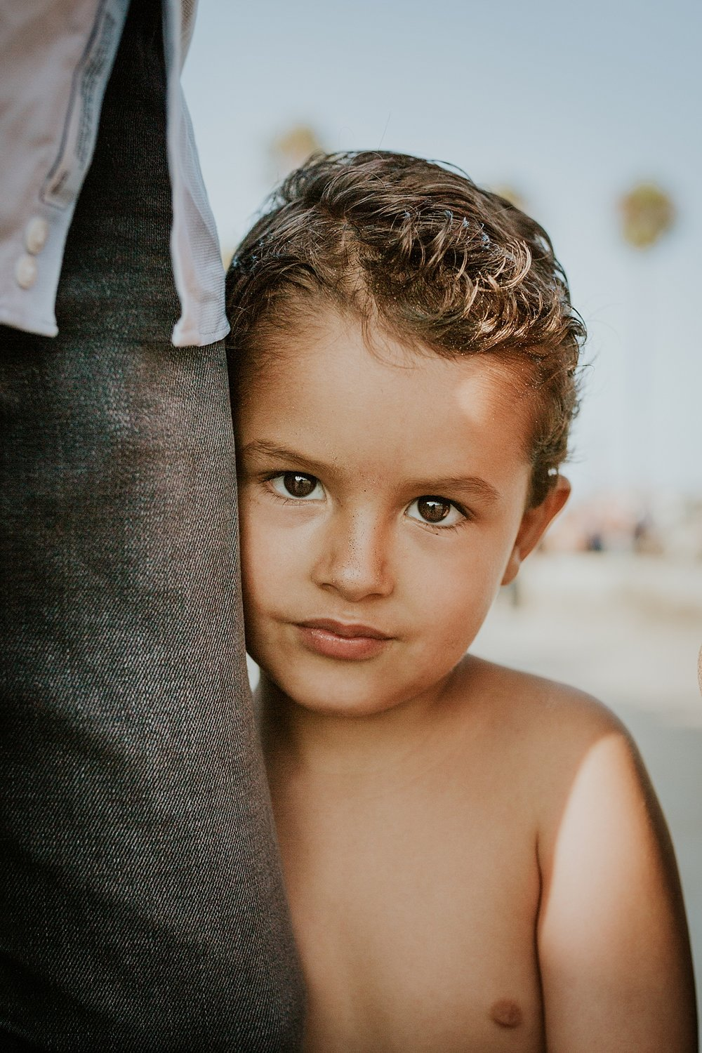 Orange County family photographer. Portrait of young boy as he hugs his dad's legs during outdoor family photo session at Huntington Beach California