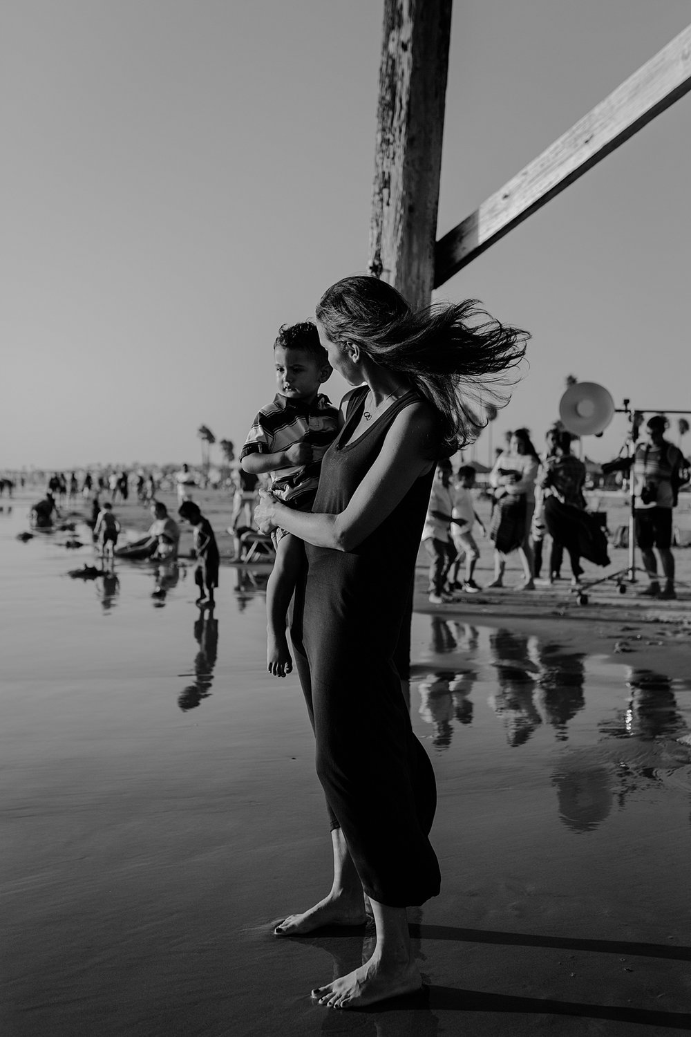 Orange County family photographer. Candid black and white photo of mom standing in the ocean water underneath the pier at Huntington Beach California