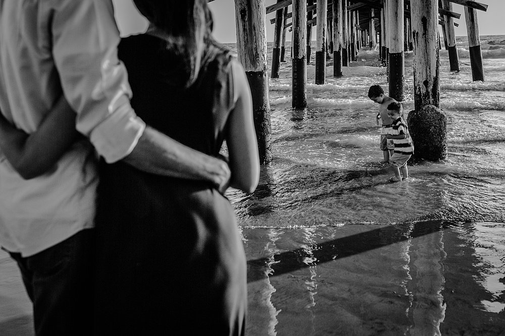 Orange County family photographer. Candid black and white photo of boys playing underneath the pier and in the ocean water while mom and dad look on at Huntington Beach California
