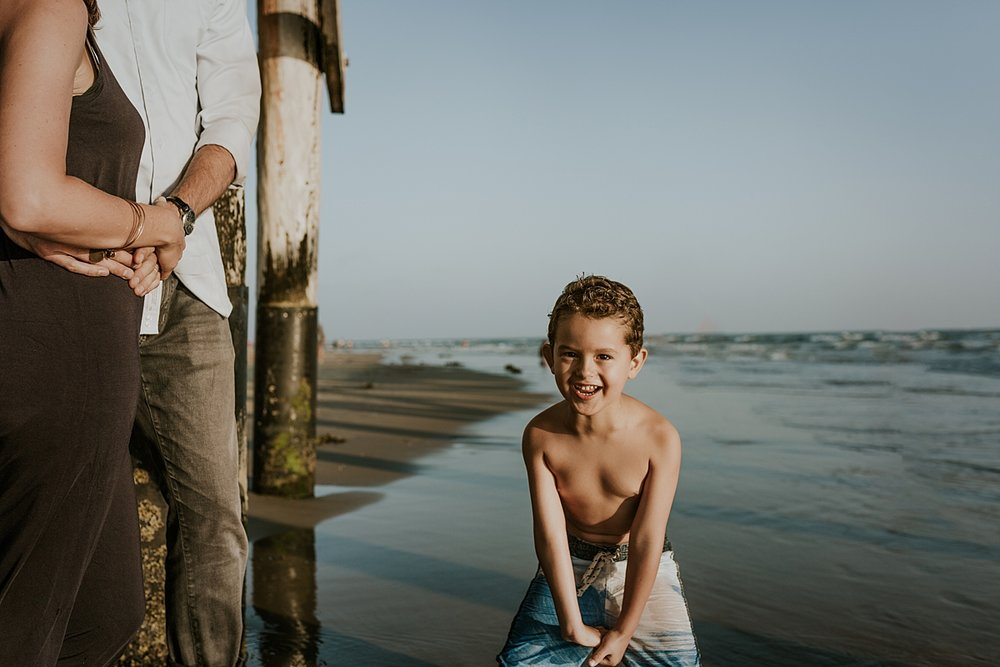 Orange County family photographer. Candid photo of son playing in the ocean water while mom and dad look on at Huntington Beach California
