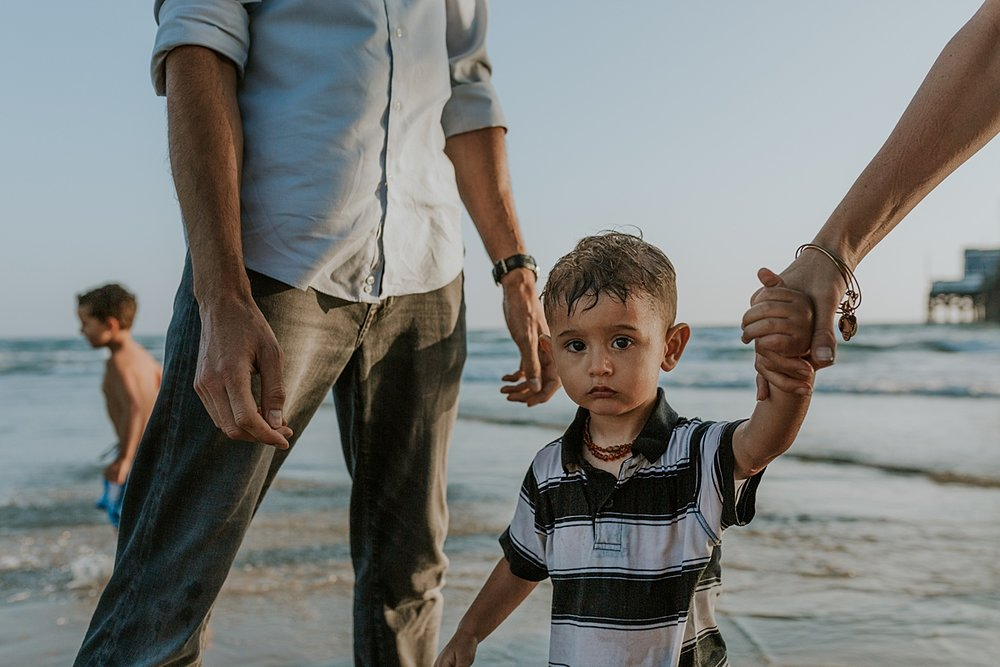 Orange County family photographer. Candid photo of toddler after he falls in the shallow ocean water during outdoor family photo session at Huntington Beach Pier California