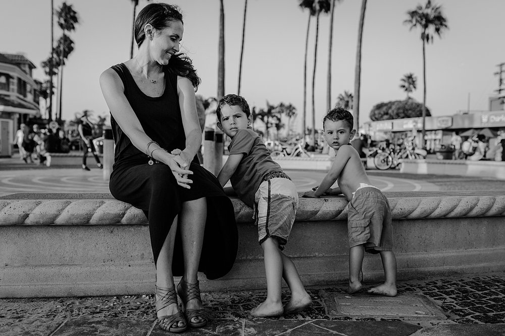 Orange County family photographer. photo of mom and her two boys standing on the streets of Huntington Beach during outdoor family photo session at Huntington Beach Pier California with Krystil McDowall Photography