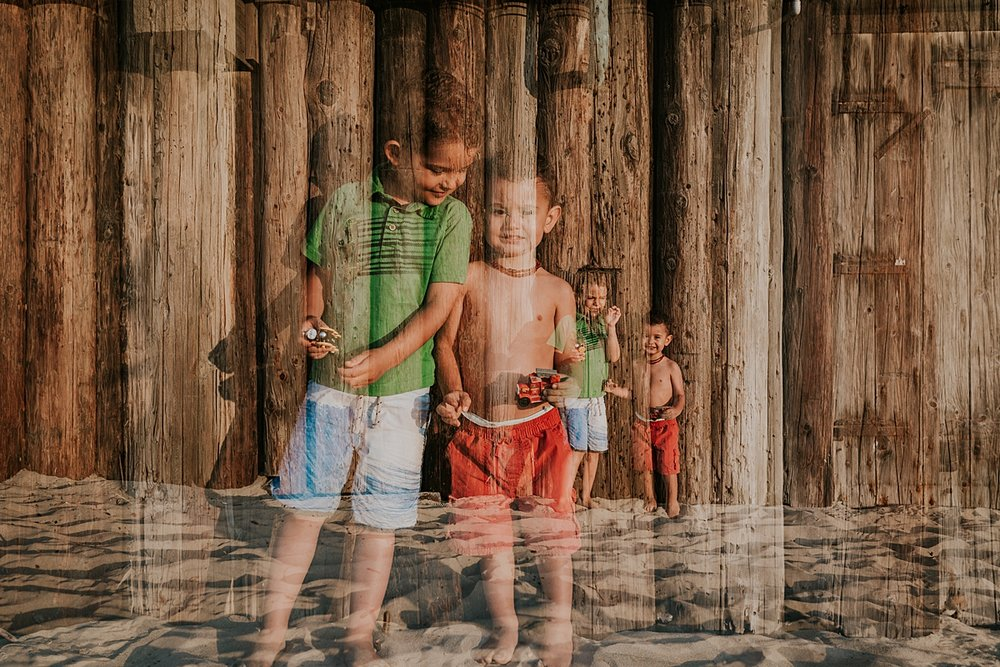 Orange County family photographer. double exposure image of brothers playing with car toys in the sand during outdoor family photo session at Huntington Beach Pier California with Krystil McDowall Photography