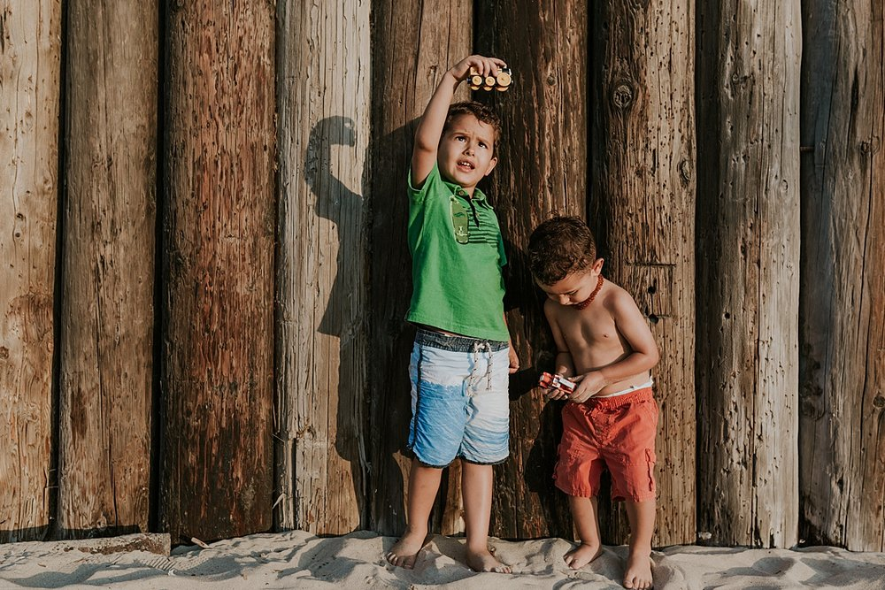 Orange County family photographer. candid photo of young brothers playing with car toys in the sand at Huntington Beach Pier during outdoor family photo session with Krystil McDowall Photography