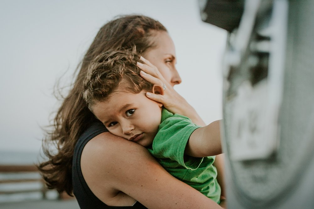 Orange County family photographer. Photo of mom hugging son while looking out at the ocean from the pier at Huntington Beach during family photo shoot with Krystil McDowall Photography