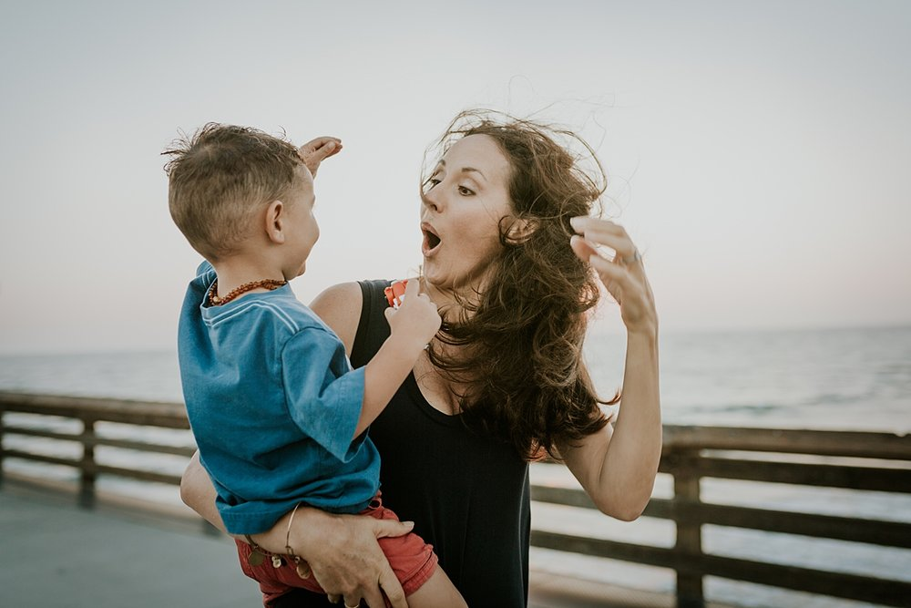 Orange County family photographer. Photo of mom walking along the pier with her youngest son at Huntington Beach during family photo shoot with Krystil McDowall Photography