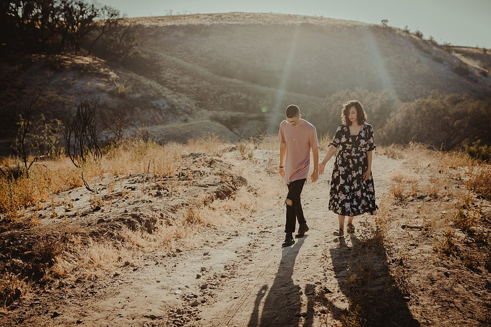 Orange County family photographer. Image of couple walking up hill at at Irvine Regional Park with sun streaming in the background