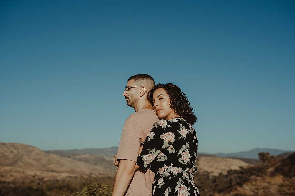 Orange County family photographer. candid photo of couple embracing atop the hills at Irvine Regional Park Orange County