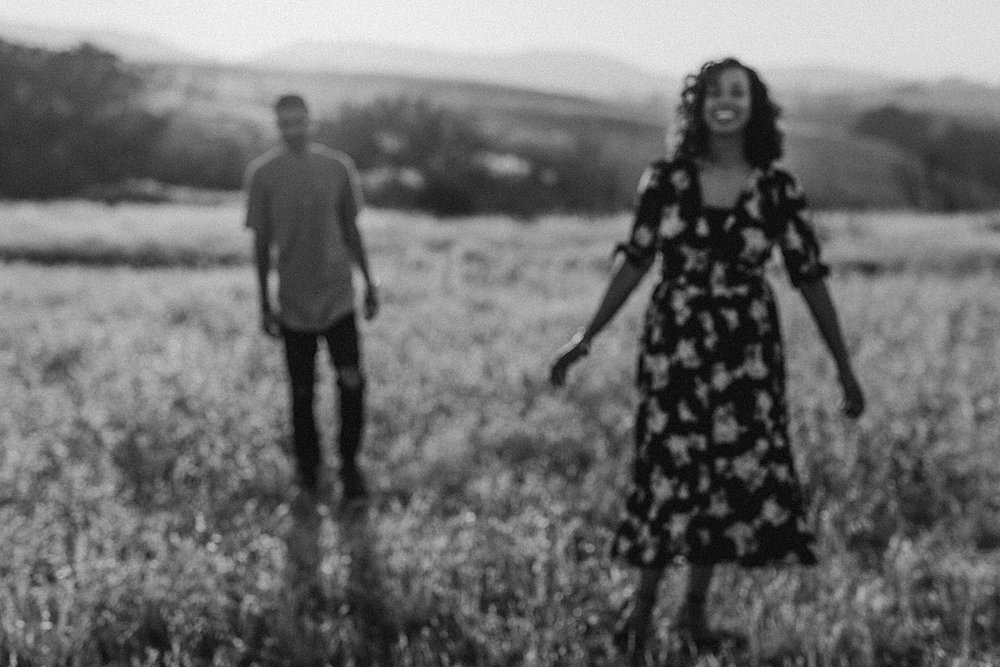 Orange County family photographer. blurred black and white photo of married couple walking through fields at couple's photo session at Irvine Regional Park
