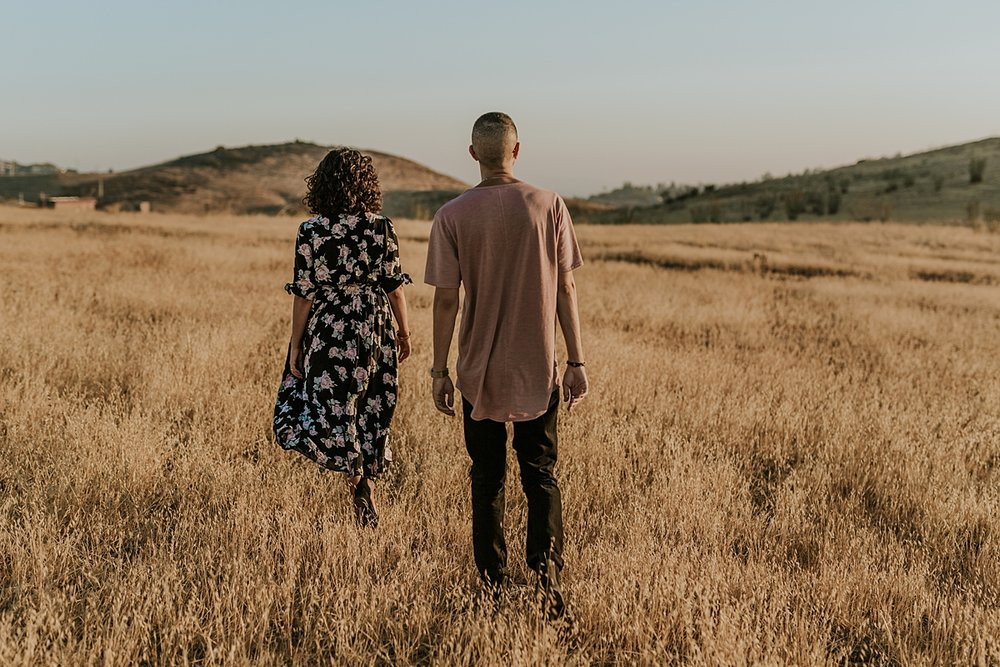 Orange County family photographer. candid photo of married couple walking amongst the fields at sunset during couple's photo session at Irvine Regional Park
