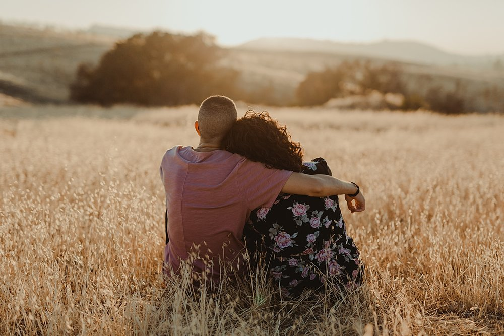 Orange County family photographer. photo of married couple sitting in park fields during outdoor couple's photo session at sunset at Irvine Regional Park