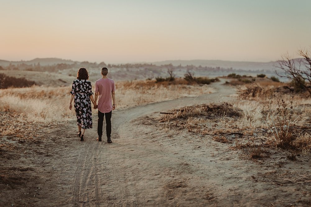 Orange County family photographer. photo of couple walking hand in hand along dirt road into the sunset at Irvine Regional Park Orange County
