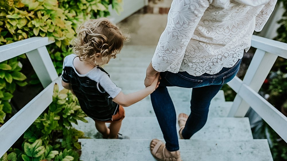 Orange County family photographer. Photo of mother and son walking hand-in-hand down the stairs to their garden to play