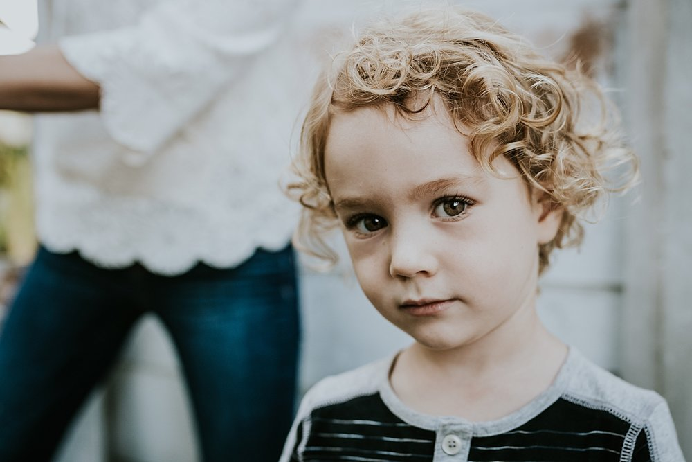 Orange County family photographer. Portrait of young curly blonde haired boy during documentary photo session with Krystil McDowall Photography