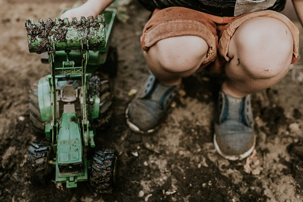 Orange County family photographer. Photo of young boy's green truck being played with his garden during documentary photo session with Krystil McDowall Photography