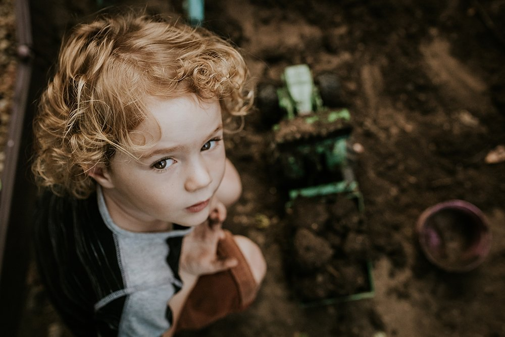 Orange County family photographer. Photo of young boy sitting in his front yard garden during documentary photo session with Krystil McDowall Photography