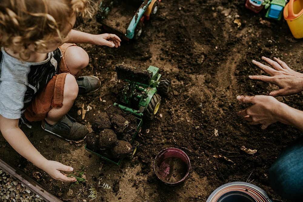 Orange County family photographer. Photo of mother and son making dirt balls in their front garden during documentary photo session with Krystil McDowall Photography