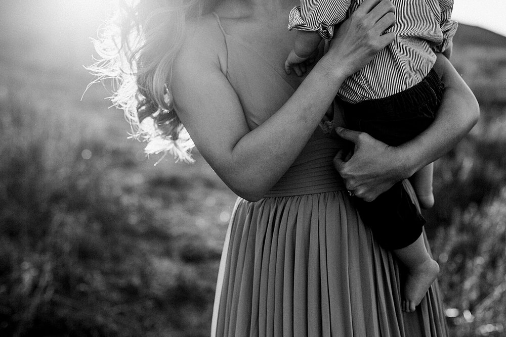 Orange County family photographer. Backlit black and white photo of mom hugging her 8 month old baby boy during lifestyle family photo shoot at Quail Hill Trailhead in California