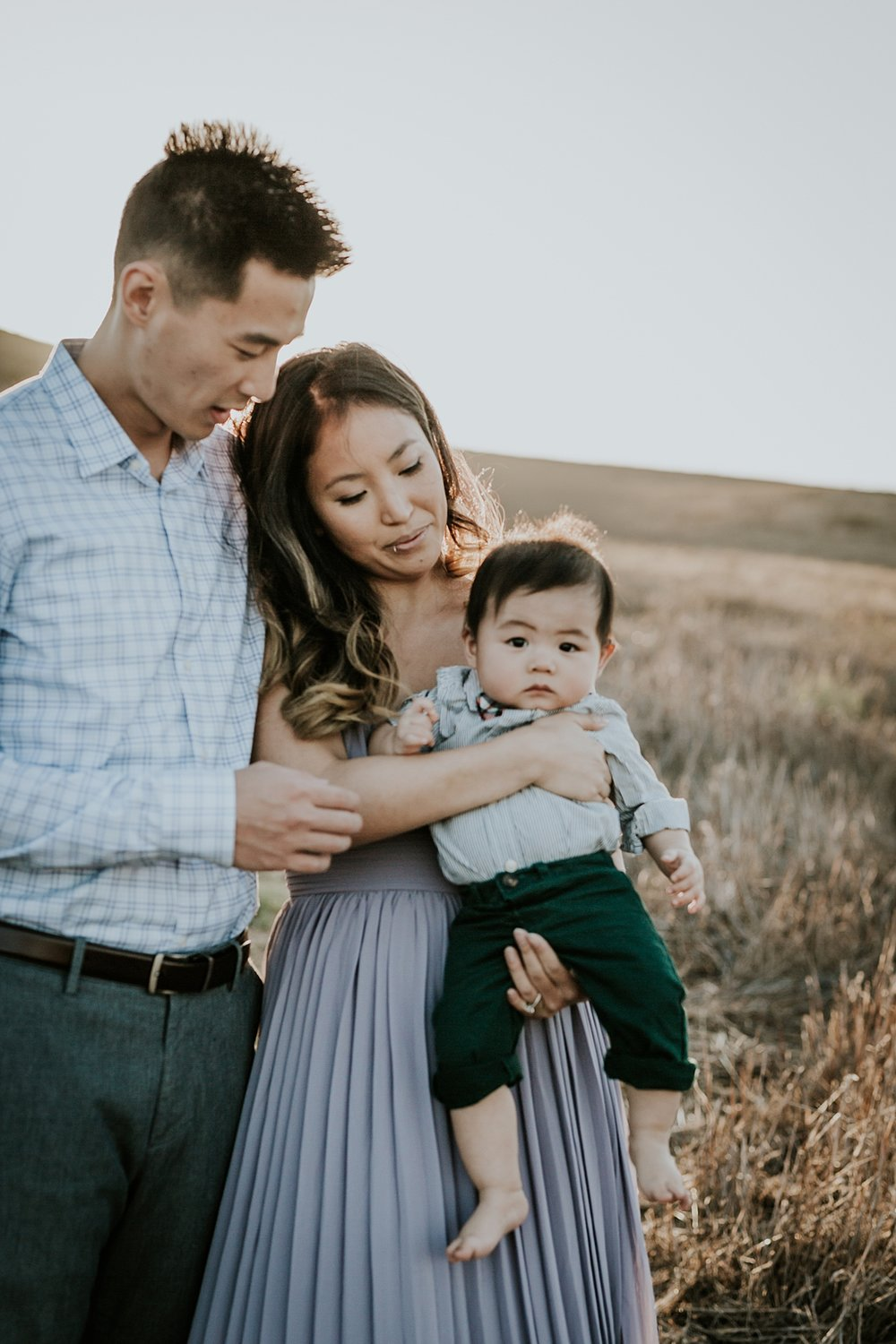 Orange County family photographer. Candid photo of of family of three during lifestyle family photo shoot at Quail Hill Trailhead in California