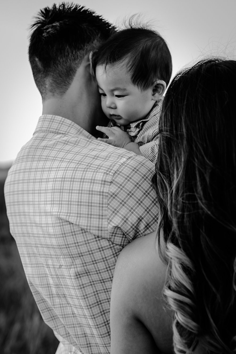 Orange County family photographer. black and white photo of dad holding baby son as he looks over dad's shoulder during family photo shoot at Quail Hill Trailhead in California