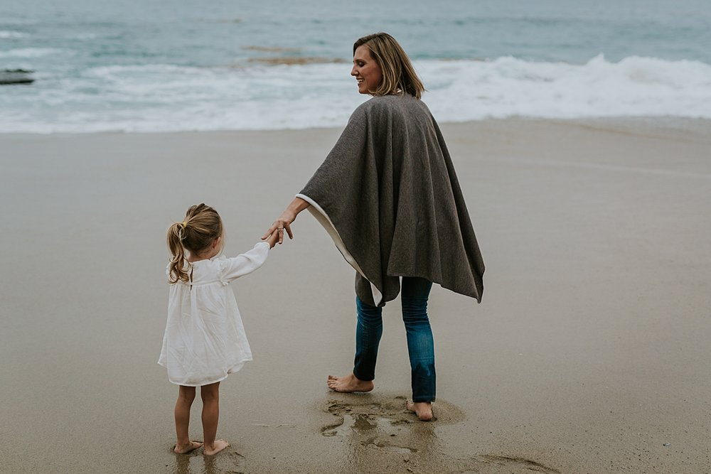 Orange County family photographer. Mom and her two year old daughter stand hand-in-hand in front of the waves at Table Rock Beach, Laguna Beach