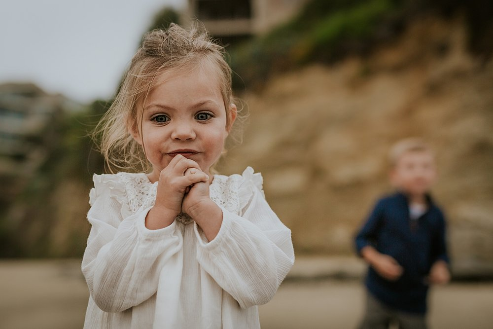 Orange County family photographer. Portrait of sweet two year old girl standing looking at the waves at Table Rock Beach, Laguna Beach