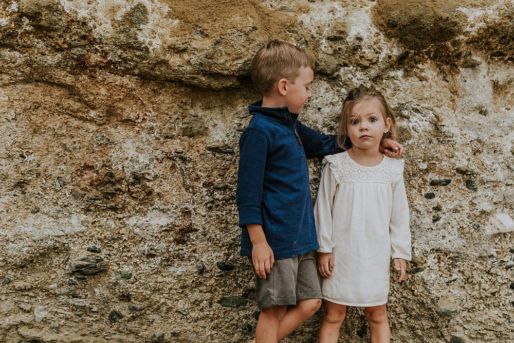 Orange County family photographer. Brother and sister candidly pose in front of bluffs at Table Rock Beach Laguna Beach during photo session with Krystil McDowall Photography