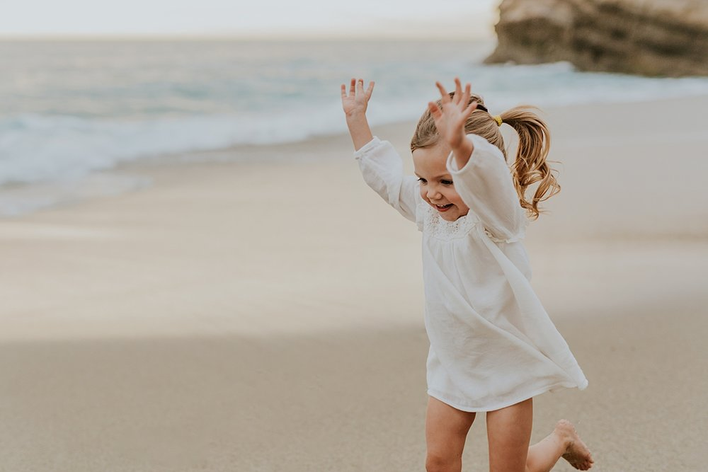 Orange County family photographer. Two year old girl runs across the sand at Table Rock Beach Laguna Beach during photo session with Krystil McDowall Photography