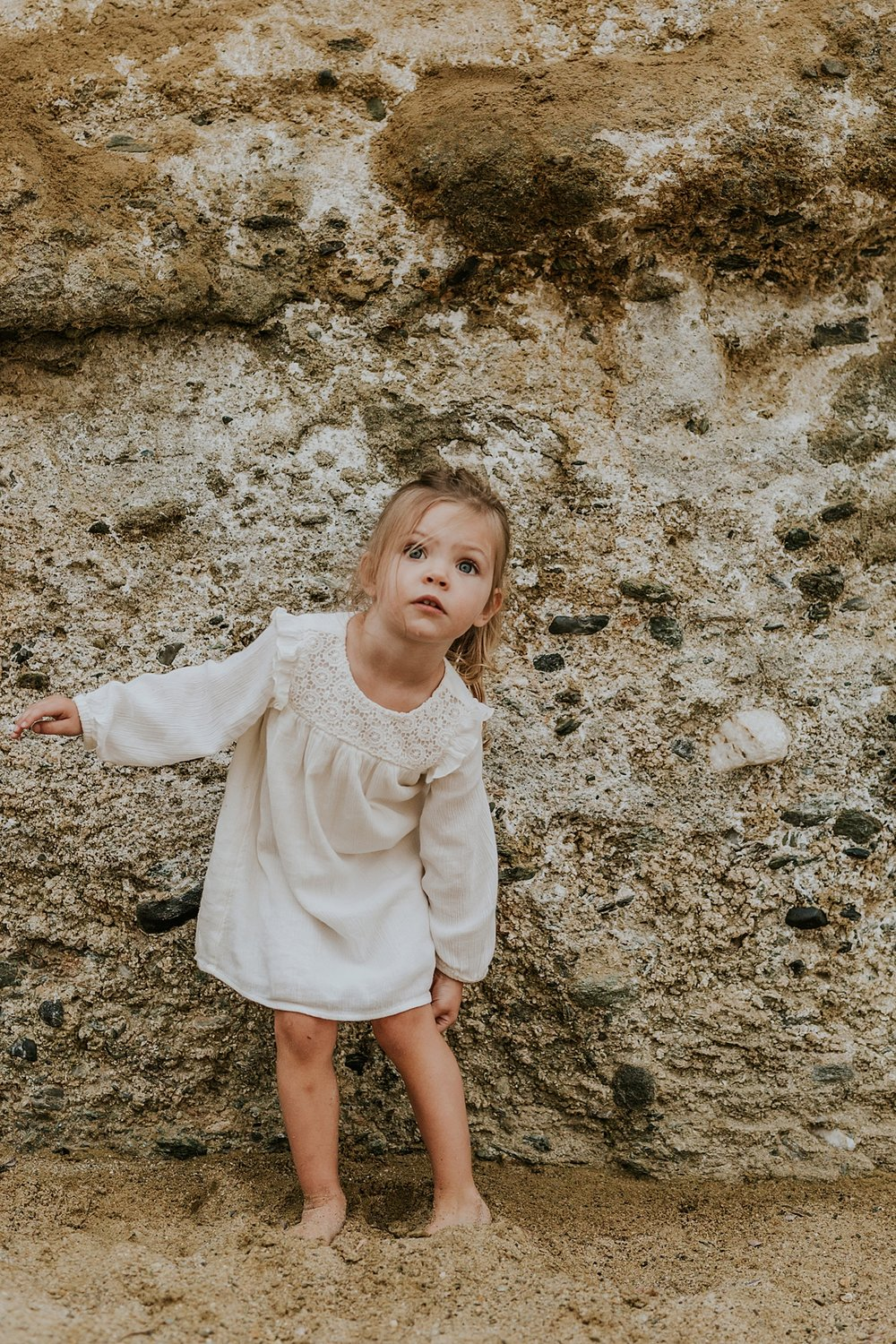 Orange County family photographer. Two year old girl candidly poses in front of bluffs at Table Rock Beach Laguna Beach during photo session with Krystil McDowall Photography